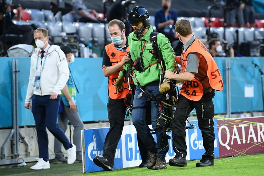A Greenpeace protestor is removed from the pitch before the match.