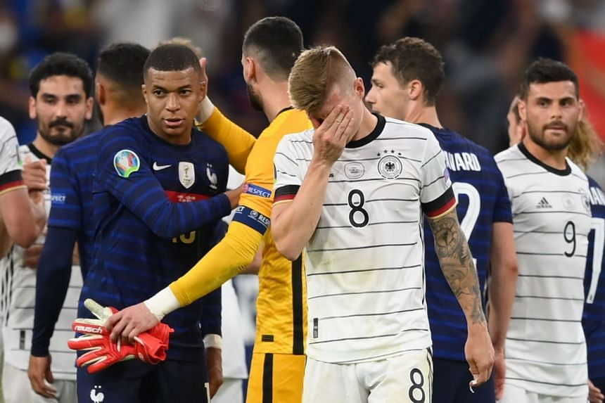 Germany's Toni Kroos looks dejected after the match as France's Kylian Mbappe looks on.