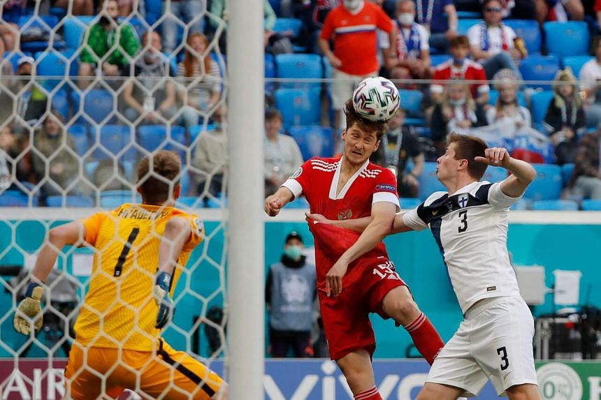 Russia's Aleksey Miranchuk (centre) heads the ball next to Finland's Daniel O'Shaughnessy (R) at the Saint Petersburg Stadium, on June 16, 2021.