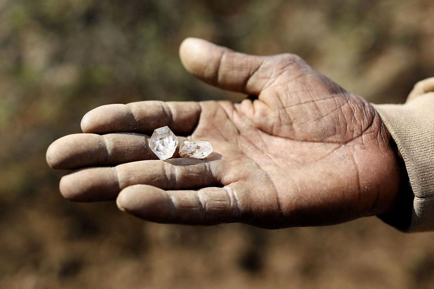 A boy holds what he believes to be a diamond at KwaHlathi village near Ladysmith, South Africa, on June 15, 2021. afp