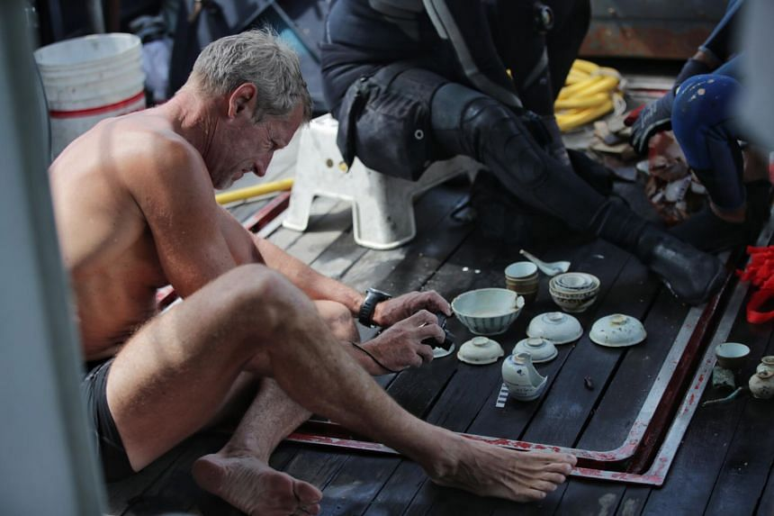 Dr Flecker takes pictures of artefacts on a vessel's desk on May 22.