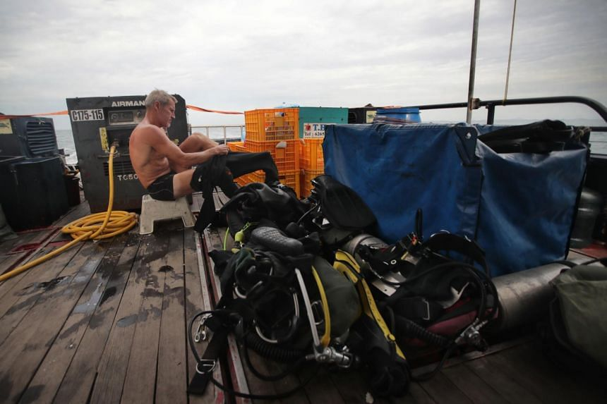 Dr Michael Flecker, a maritime archaeologist, puts on his wetsuit as he prepares for a dive on May 22.