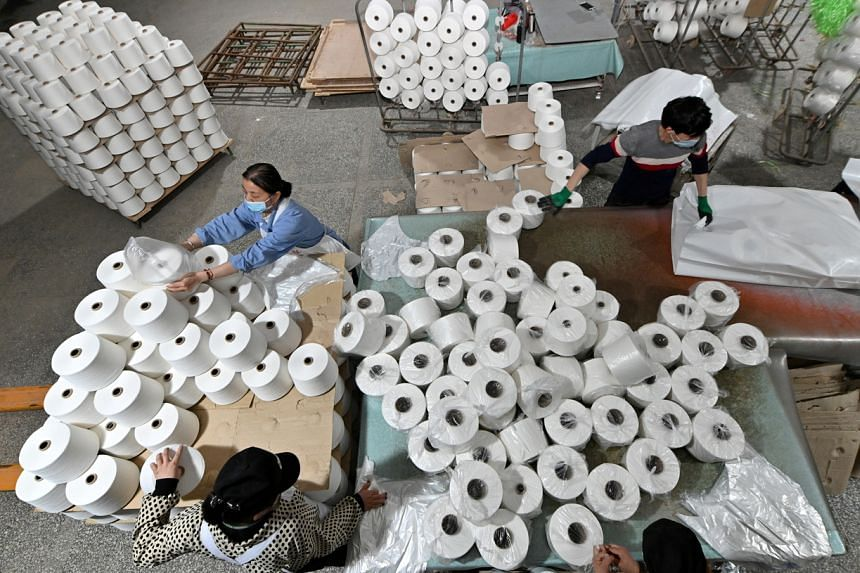In this photo taken on April 1, 2021, workers are seen on the production line at a cotton textile factory in Korla, Xinjiang Uighur Autonomous Region.