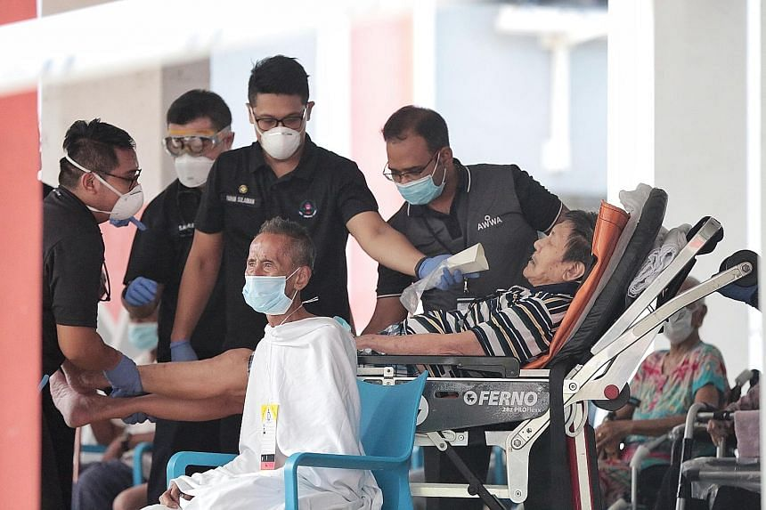 Evacuees from Block 123 Ang Mo Kio Avenue 6 being attended to by the Singapore Civil Defence Force (SCDF) yesterday. Seven residents were taken to Singapore General Hospital, Khoo Teck Puat Hospital and National University Hospital for smoke inhalati