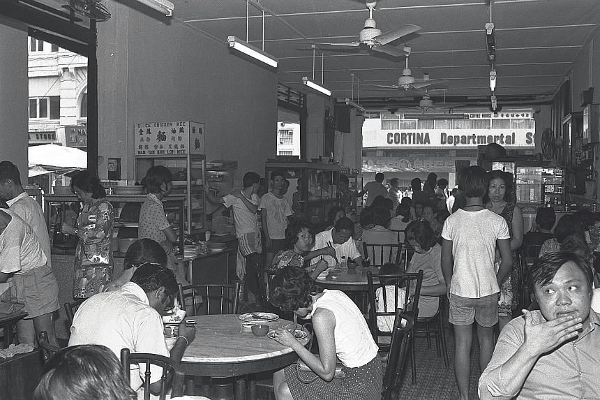 A crowded kopitiam in Hock Lam Street, one of Singapore's well-known eating spots that had to make way for urban renewal. People eating at a coffee shop in Serangoon Central in May this year. With the creation of multiracial housing towns, kopitiams