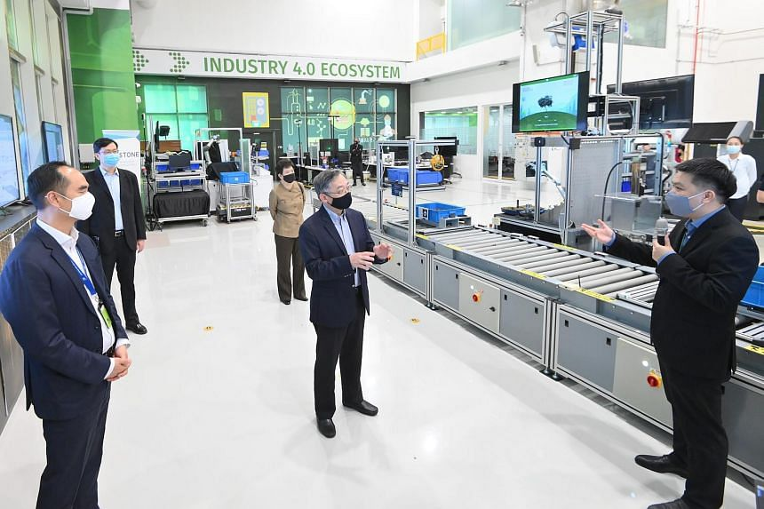 Minister for Trade and Industry Gan Kim Yong (centre) being shown the A*Star-Arcstone joint lab by Arcstone CEO Willson Deng (right) on June 17, 2021.