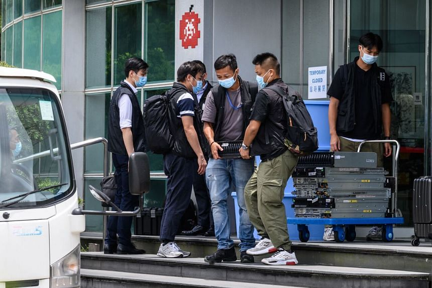 Police officers taking computer equipment from the offices of Apple Daily in Hong Kong on June 17, 2021.