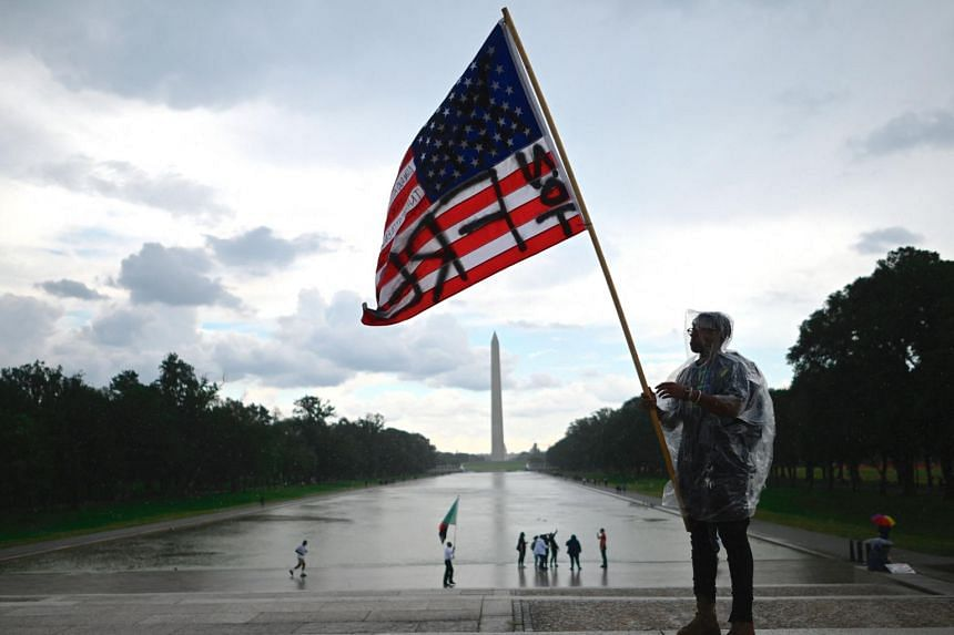 """A demonstrator waves an American flag with the words """"Not Free"""" painted on it during a Juneteenth march and rally in Washington, DC, on June 19, 2020."""