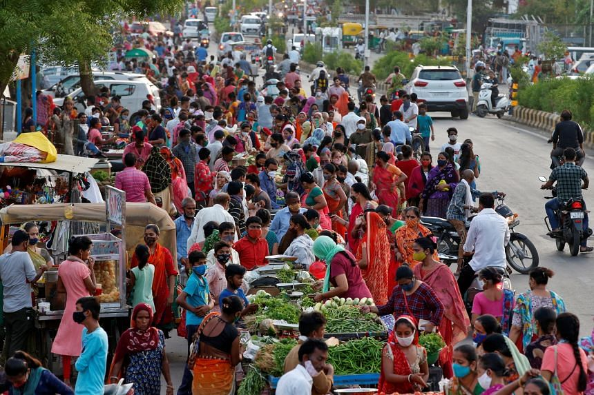 People shop at a roadside vegetable market after authorities eased coronavirus restrictions in Ahmedabad, India, on June 15, 2021.