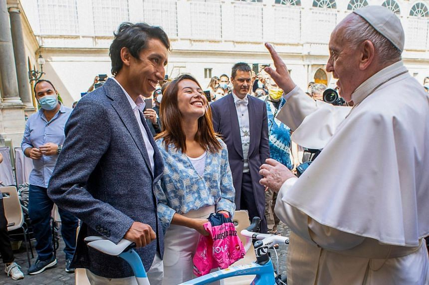 Colombian cyclist Egan Bernal (left) presents Pope Francis with an Ineos Grenadier team jersey and a bicycle,  at The Vatican, on June 16, 2021.