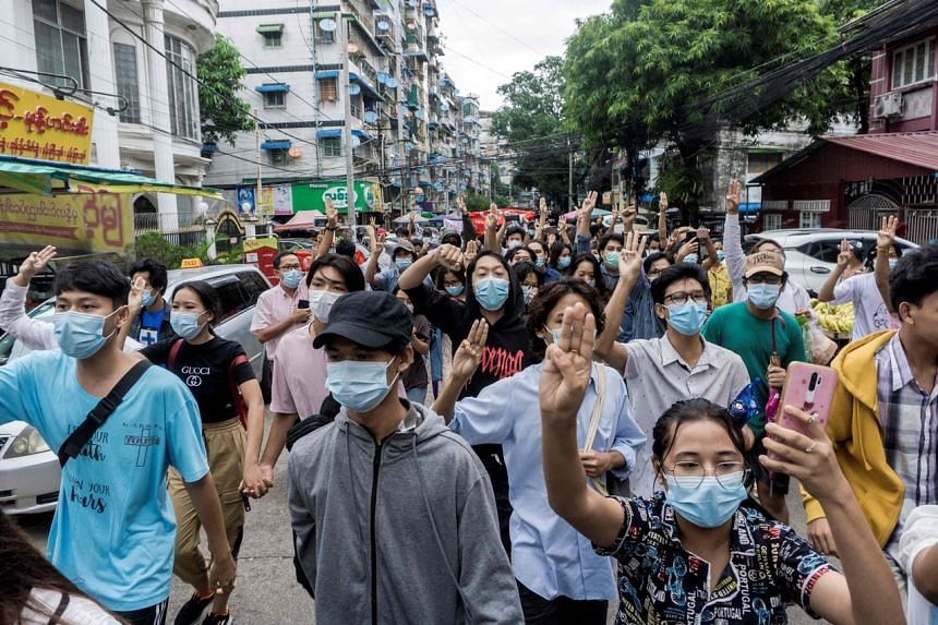 Protesters make the three-finger salute in a flash mob demonstration in Yangon, on June 14, 2021.