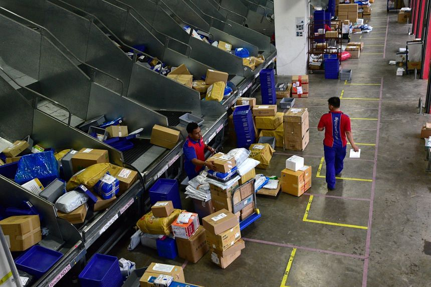 Workers collecting parcels from a cross-belt sorter at SingPost's Regional eCommerce Logistics Hub in Greenwich Drive.