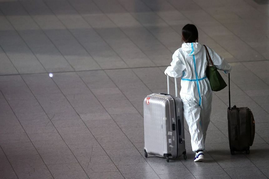 A passenger wears a PPE (personal protection equipment) suit as she walks through a terminal Frankfurt airport in Germany, in May 2021.