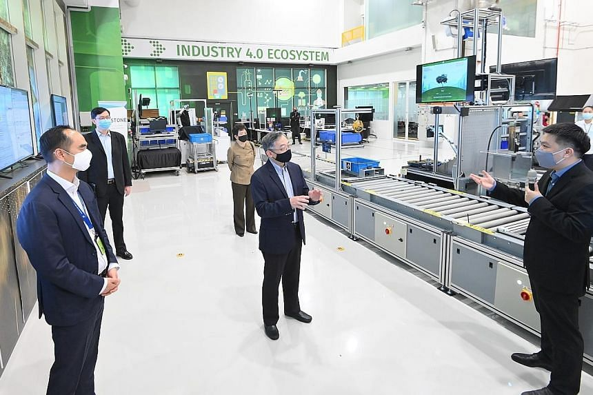 Minister for Trade and Industry Gan Kim Yong (centre) visiting the new facility set up jointly by A*Star and local manufacturing software company Arcstone yesterday. Sharing the lab details is Mr Willson Deng, chief executive of Arcstone. At the lab'