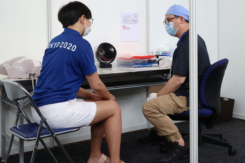 A doctor speaking to a woman, who is involved in the Tokyo Olympics, ahead of her vaccination, at the Tokyo Metropolitan Government office on June 18, 2021.