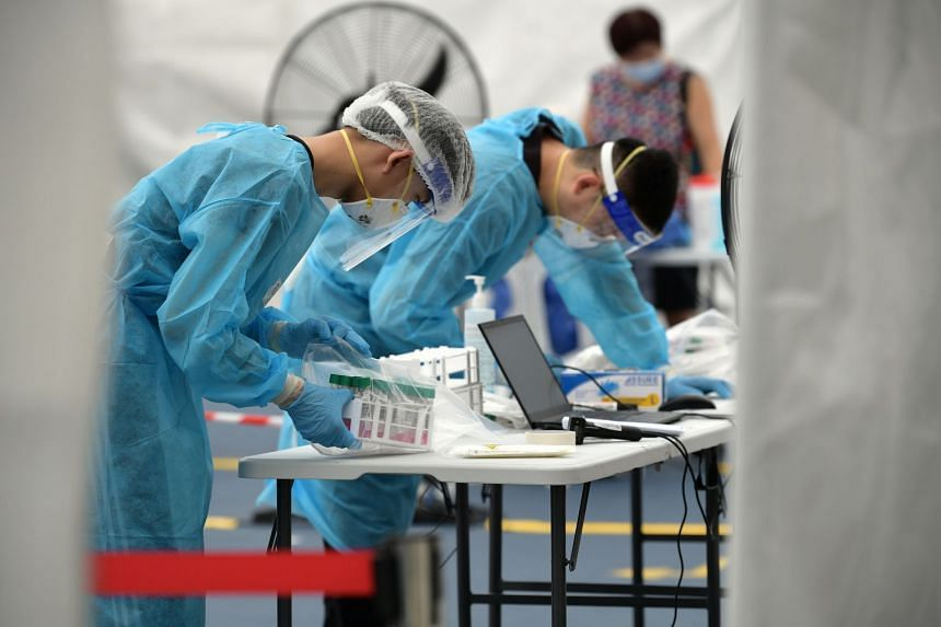 Staff at the Covid-19 test centre at Block 685A Hougang Street 61 packing swab samples on June 5, 2021.