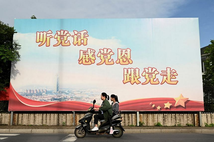 """A propaganda board that reads """"Listen to the party, appreciate the party, follow the party"""" along a street in Huaxi village in China."""