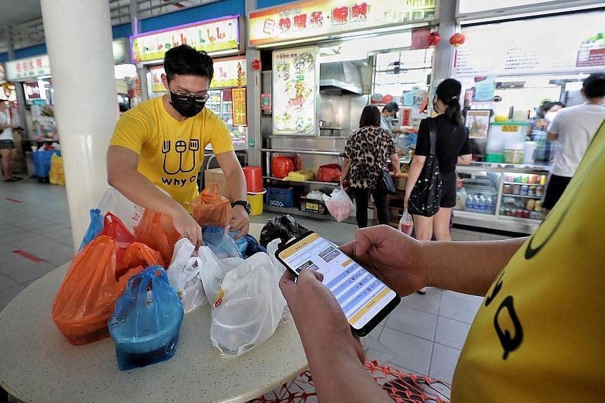 Staff of food delivery platform WhyQ organising orders placed on the app before handing them to delivery riders at Tiong Bahru Market and Food Centre on June 15, 2021.