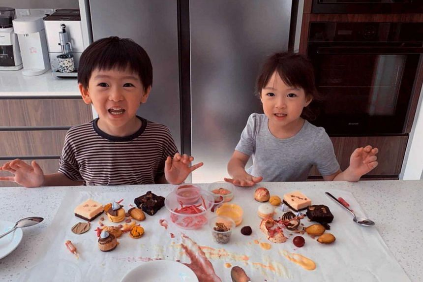 Siblings Cooper Foo and Riley Foo having a blast with the dessert-painting kit offered by Splat Paint House.