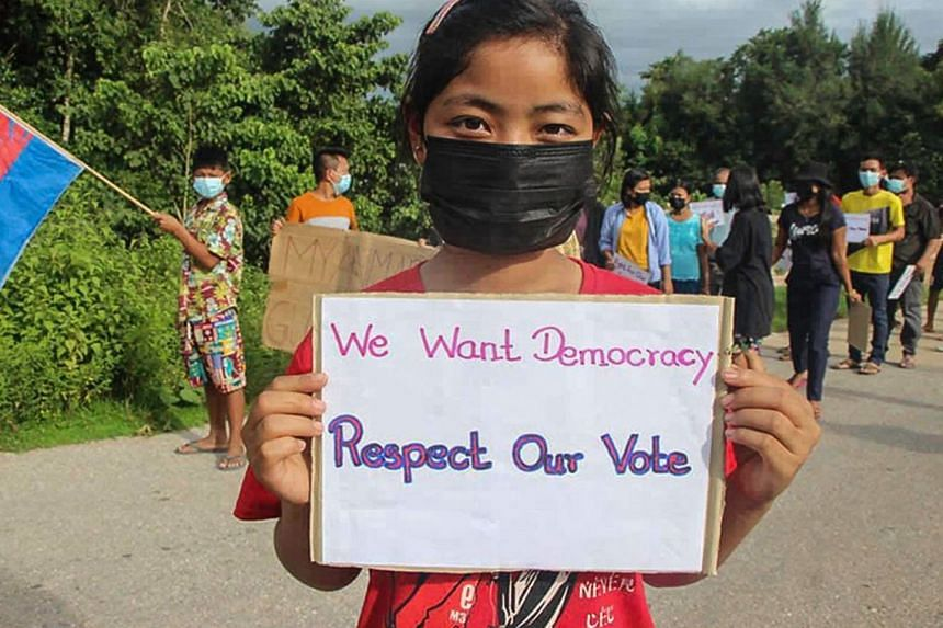 A protester holds a sign during a demonstration against the military coup in Dooplaya district in Myanmar's Karen state.