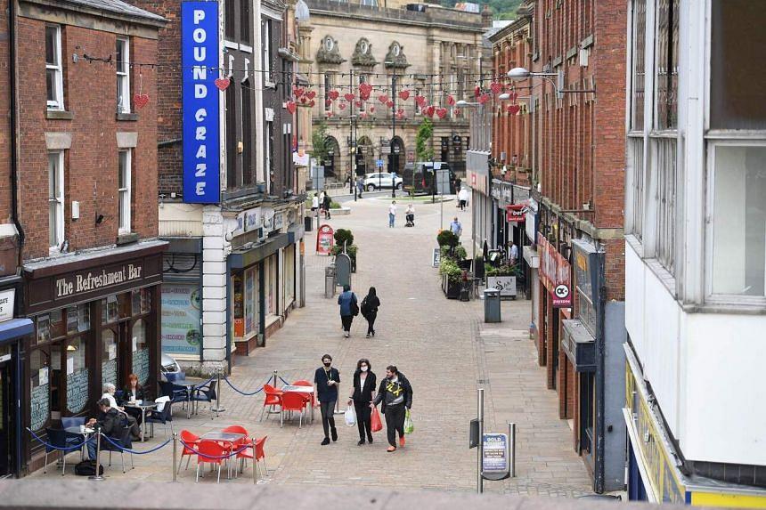 Pedestrians walk along an almost empty shopping street in Blackburn, north west England, on June 16, 2021.