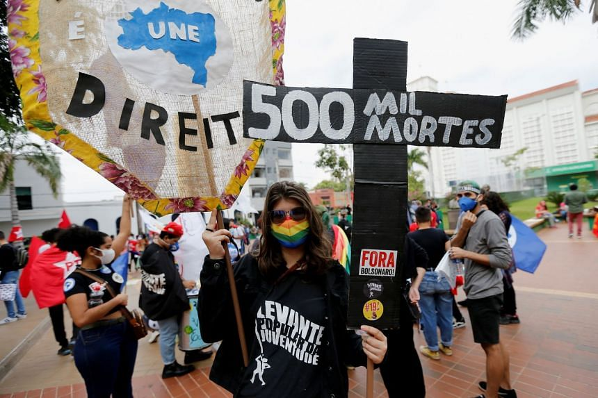 """A person holds a cross reading """"500.000 deaths"""" as people protest against Brazil's President Jair Bolsonaro and his handling of the coronavirus pandemic in Cuiaba, Brazil, on June 19, 2021."""