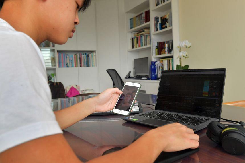 Liu Yue Heng doing work on his laptop at home.