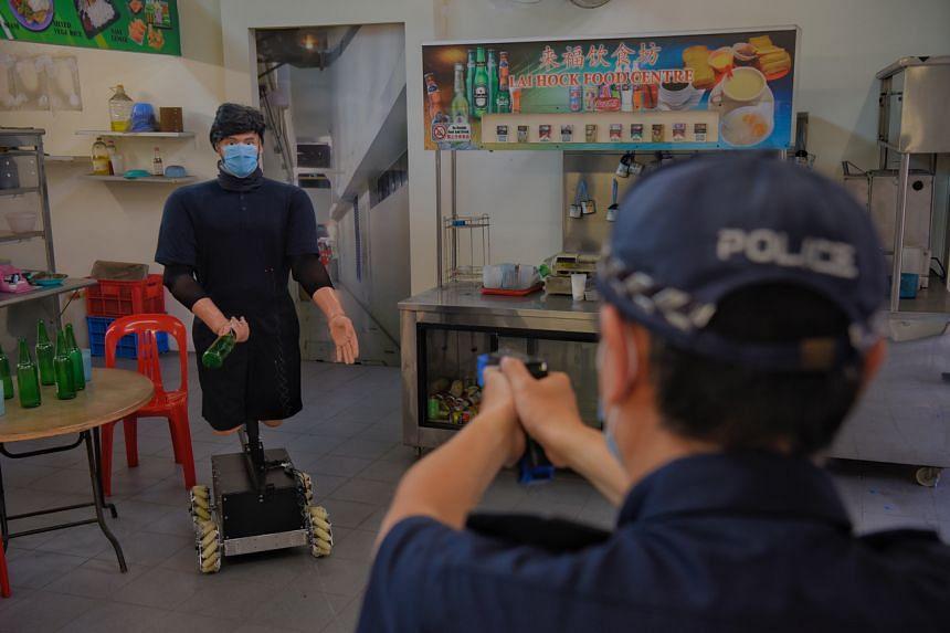 A police officer fires his Taser at the Mobile Taser Training Target, a training bot, on June 18, 2021.