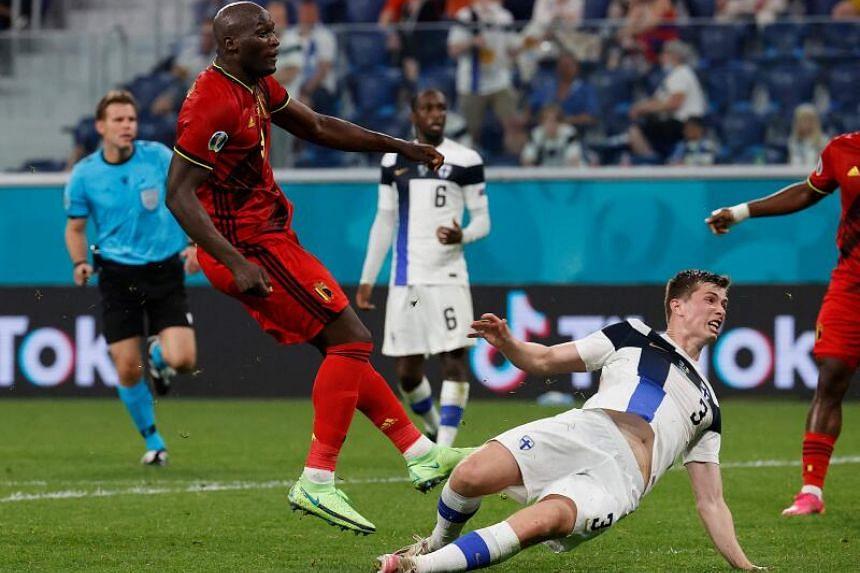 Belgium's forward Romelu Lukaku (left) shoots to score the second goal for his team on June 21, 2021.