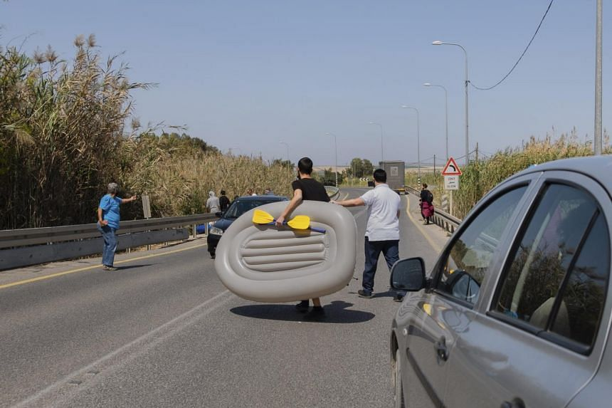 A resident of Beit Shean carries his raft to the Asi River along a fast and dangerous stretch of road near Kibbutz Nir David in northern Israel.
