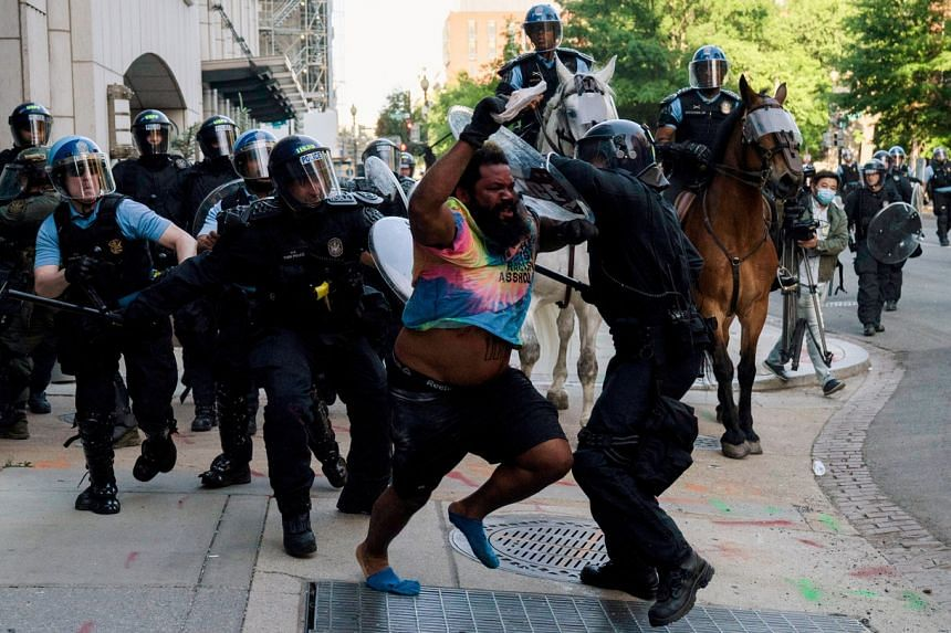 In a photo from June 1, 2020, riot police clash with a protester as they clear Lafayette Park.