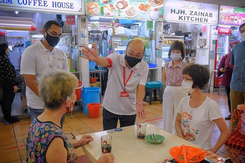 A National Environment Agency officer, with Senior Minister of State Amy Khor (standing, right), reminding patrons at North Bridge Road Market and Food Centre yesterday to clear their used plates.