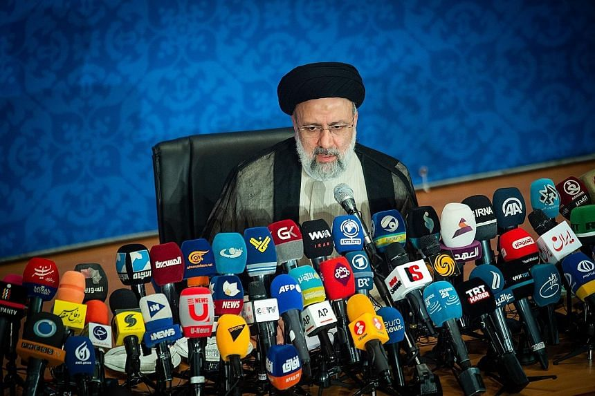 """Iran's president-elect Ebrahim Raisi holding his first news conference following his election victory in Teheran on Monday. Mr Raisi, who takes office in August, said his administration's policies would be """"revolutionary""""."""