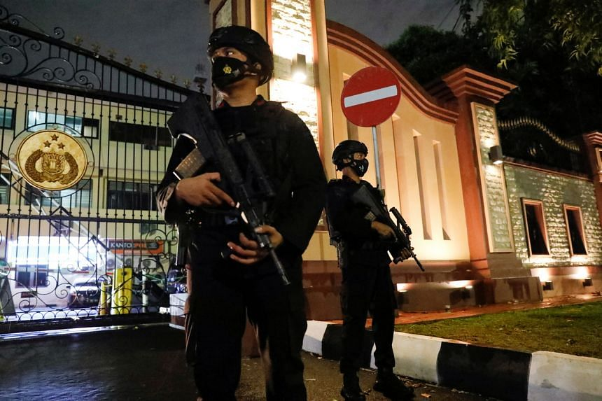 Armed police officers standing guard at the gate of the national police headquarters in Jakarta following a suspected militant attack on March 31, 2021.