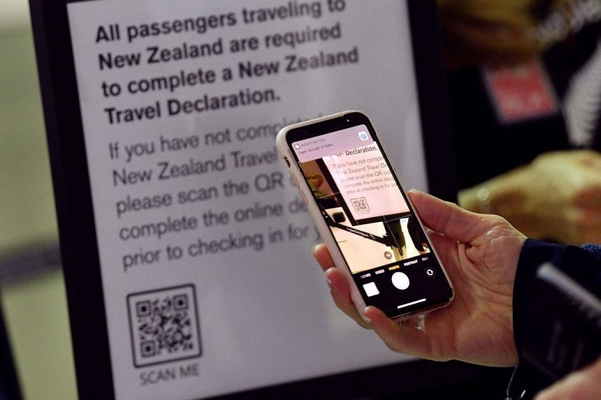 An April 2021 photo shows a passenger scanning a barcode to complete a travel declaration for a New Zealand flight at Sydney International Airport.