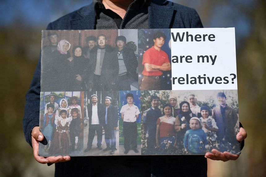 A member of the Uighur community holds a placard during protests in London calling on Britain's parliament to vote to recognise alleged persecution of China's Muslim Uighur minority as genocide, in April 2021.