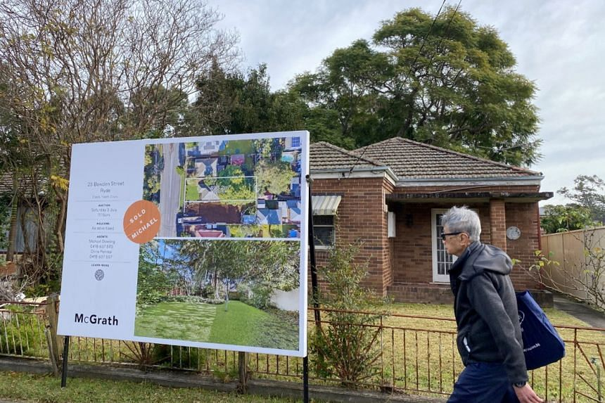 A man walks past a derelict home, which sold for A$1.6 million, in Sydney, on June 23, 2021.