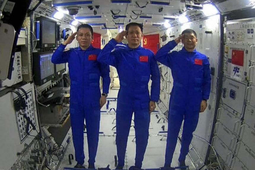 Chinese astronauts (from left) Tang Hongbo, Nie Haisheng and Liu Boming saluting as they speak with Chinese President Xi Jinping from the core module Tianhe on June 23, 2021.