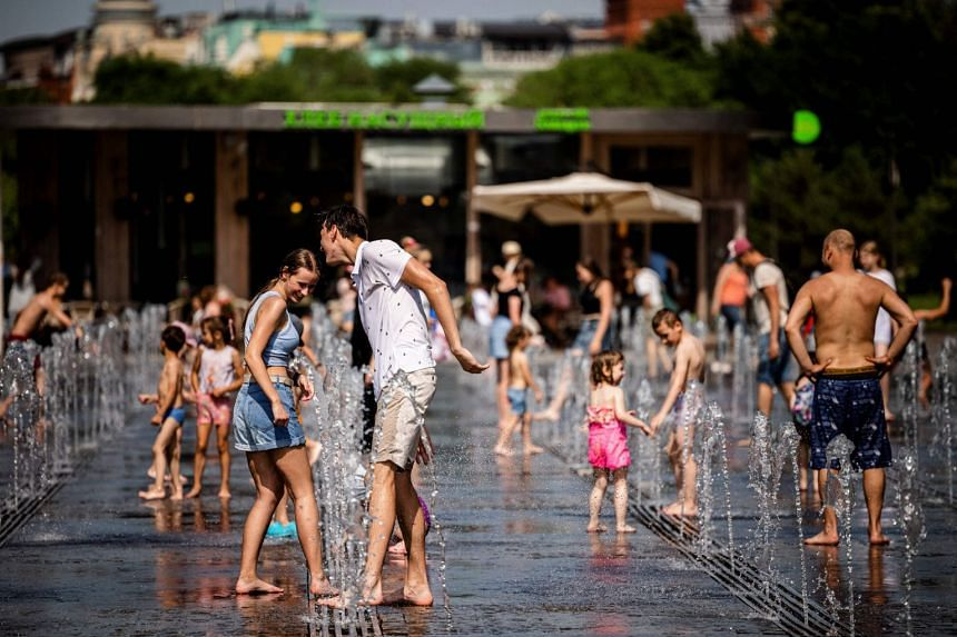 People cool off at a water fountain on June 21, 2021, in Moscow's Gorky Park.