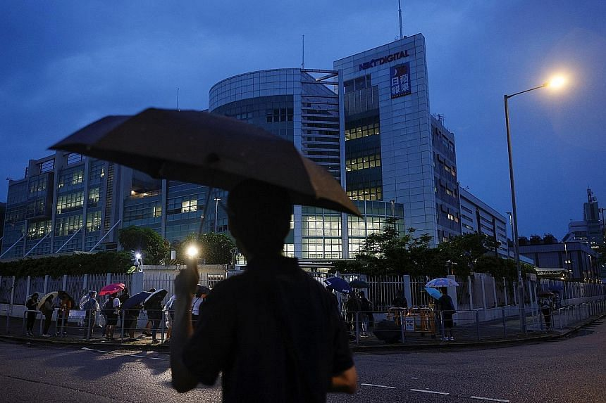People outside the headquarters of Apple Daily and its publisher Next Digital in Hong Kong yesterday.