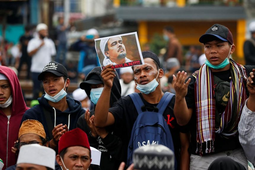 A protester holding a picture of Islamic cleric Rizieq Shihab during a demonstration in Jakarta on June 24, 2021.