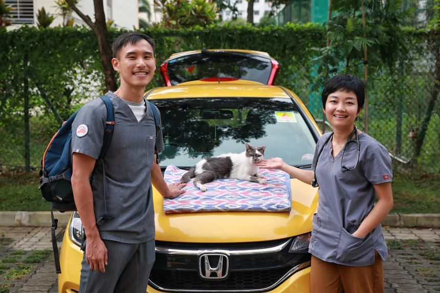 Dr Angeline Yang (right) with her husband Mr Choo Zheng Hao, their adopted cat Aunty Rosie and their yellow hatchback vehicle from which they run VetMobile.