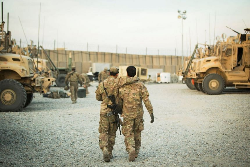 A 2014 photo shows a US soldier walking with his unit's Afghan interpreter before a mission.