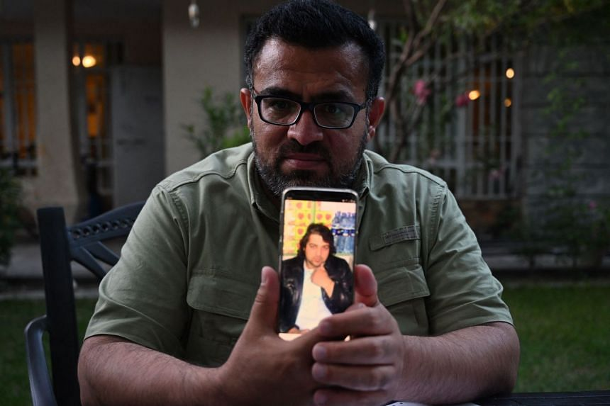 Ahmad Siyar Anwari, a former interpreter working for the French military, holds a phone with a picture of Abdul Basir.