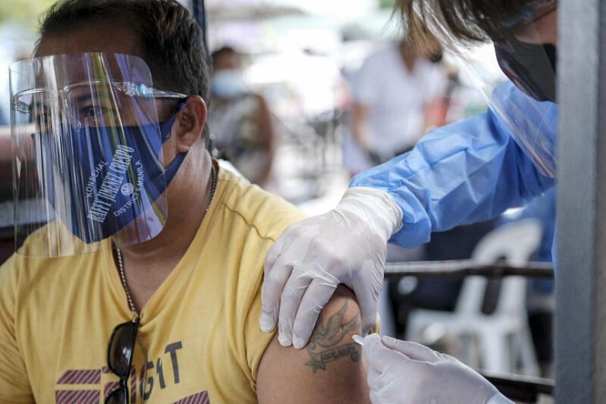 A motorcycle taxi driver receives a dose of the Sinovac Biotech Ltd vaccine at a Covid-19 drive-thru vaccination site set up at the Philippine International Convention Center in Manila, the Philippines, on June 22, 2021.