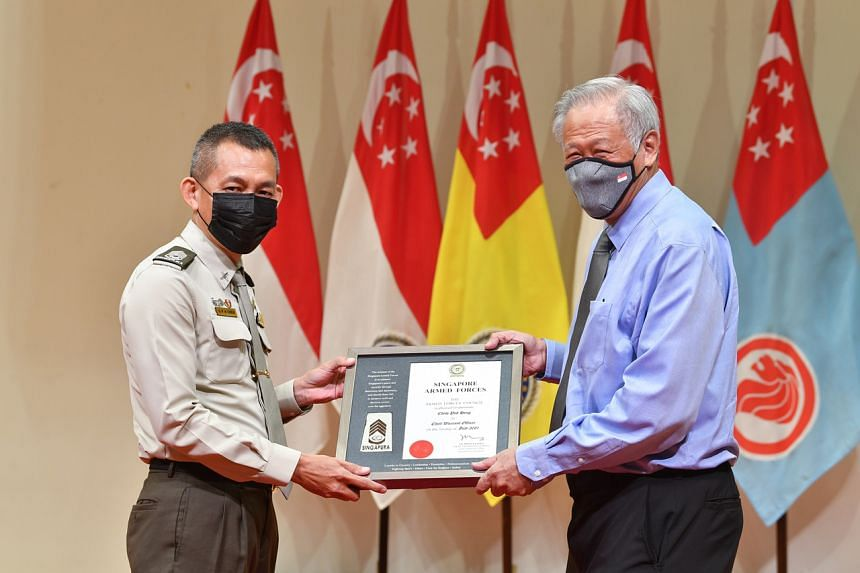 Senior Warrant Officer Chew Poh Heng receiving his promotion certificate from Defence Minister Ng Eng Hen.