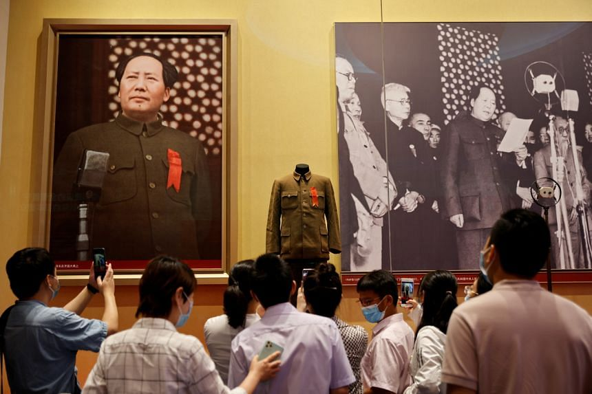 People looking at images of Mao Zedong at the Museum of the Communist Party of China in Beijing, on June 25, 2021.