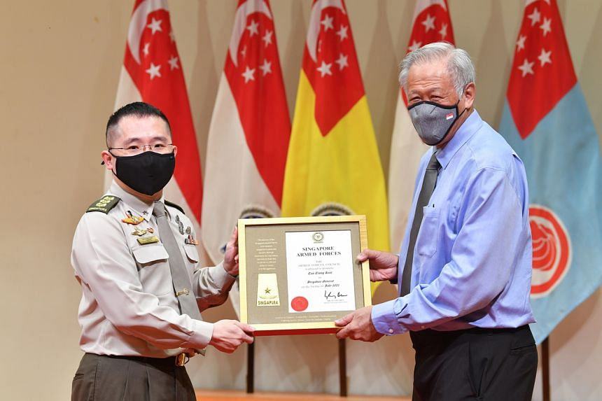 Colonel Tan Tiong Keat receiving his promotion certificate from Defence Minister Ng Eng Hen.