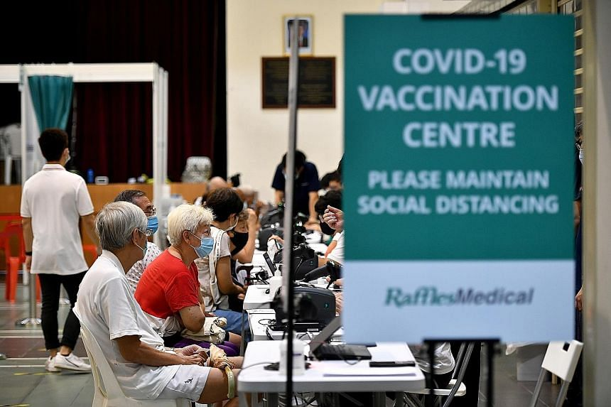 """People at the Covid-19 vaccination centre in Hong Kah North Community Club in March. On Thursday, Health Minister Ong Ye Kung said about 75 per cent of people aged 60 and older had received at least one dose of the vaccine, but this was """"not enough""""."""