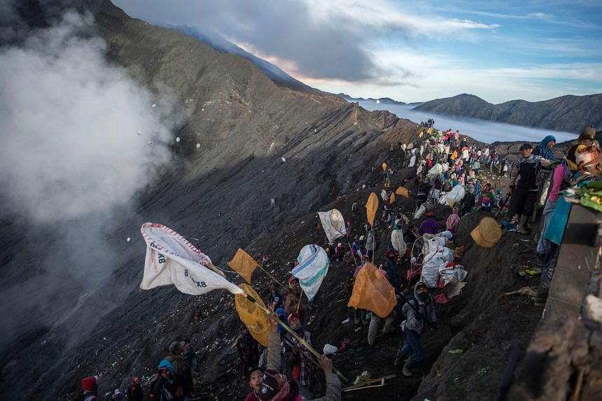 Villagers try to catch offerings thrown by the Tengger tribe people on the slopes of Mount Bromo's crater.